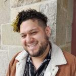 Individual with curly hair smiling at camera