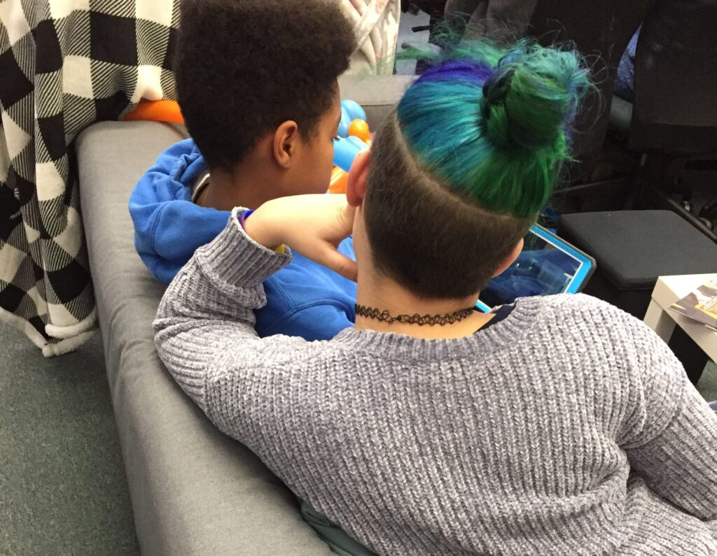 two youth sitting on a sofa looking at a tablet.