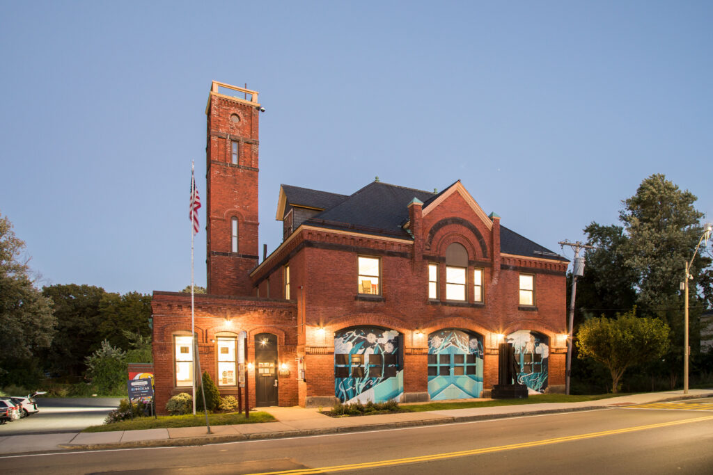 Photo of renovated firehouse lit up at dusk.
