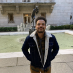 Adult standing in front of a fountain, with hands tucked in pocket of midweight jacket. Joel is smiling up into the camera. He has light brown skin; short, curly hair; and facial hair.