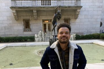 Joel stands in front of a fountain, smiling up into the camera.